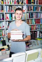 teenage boy with book pile in shop.