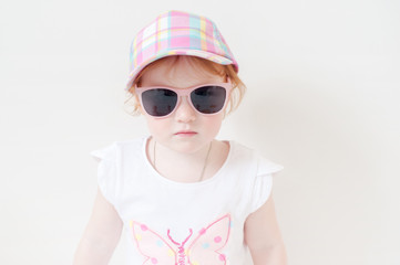 Girl in a pink cap and glasses on the white background