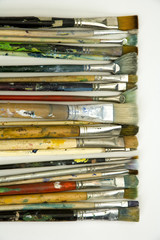 Well used artists paintbrushes on a white paper background