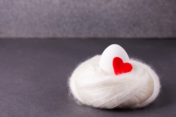 Easter concept, the origin of life, love and purity - a white egg with a red heart lies in a soft cozy warm nest on a gray background