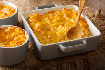 Homemade casserole mac and cheese in a baking dish close-up on a table. horizontal