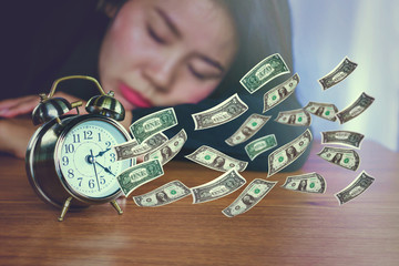 time is money concept with alarm clock on desk and paper currency flying away  ,lazy Asian woman sleeping in background