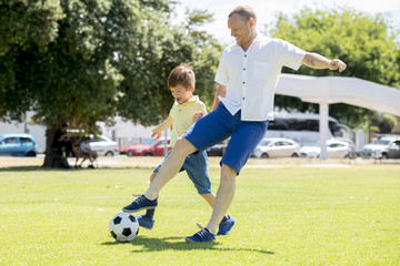 young happy father and excited little 7 or 8 years old son playing together soccer football on city park garden running on grass kicking the ball