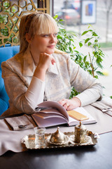 Middle age business lady at the restaurant decides her business. The concept of a business woman working in a big city. Problems and joys of  cityzen women