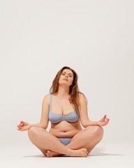 Beautiful girl in underwear sitting on floor and meditating.