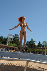 red-haired girl in a swimsuit jumping on a trampoline