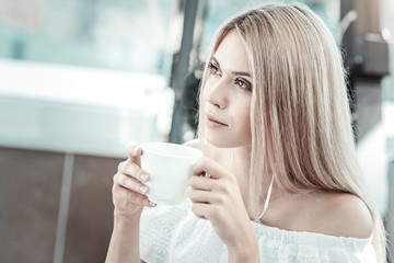 Delicious drink. Attractive blonde young woman holding a cup and drinking coffee while sitting in the cafe