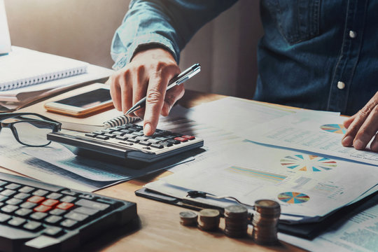 businessman using calculator with hand holding pen working in office. concept finance and accounting