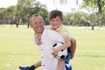 young happy father carrying on his back excited 7 or 8 years old son playing together soccer football on city park garden posing sweet and loving