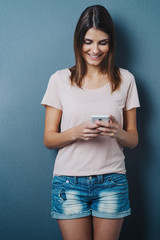 Pretty trendy young woman using a mobile phone