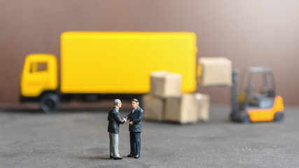 miniature businessman shaking hand with container truck and carton products goods box background in distribution warehouse factory.