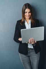 Attractive businesswoman using a handheld laptop
