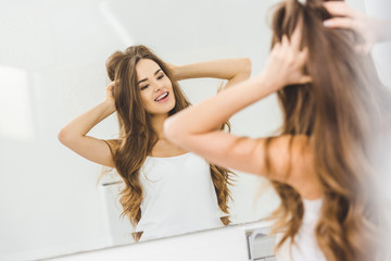 mirror reflection of cheerful beautiful young woman in bathroom at home