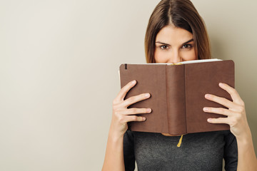Fun young woman peering over a book