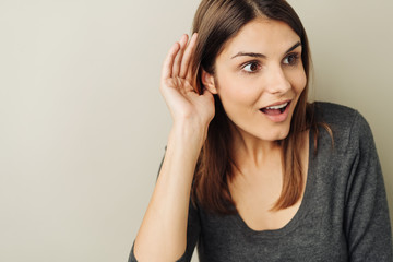Excited young woman listening to gossip
