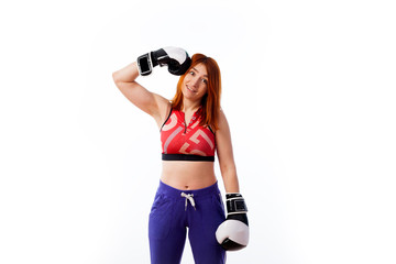 young red-haired woman in sportswear and black and white boxing gloves smiles and strikes herself on the head box on white isolated background...