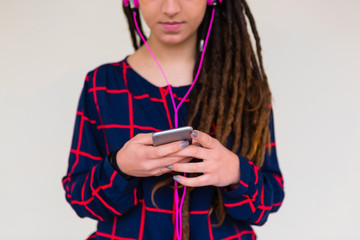 Urban Young Woman with Dreadlocks Listen to Music with a Mobile Phone