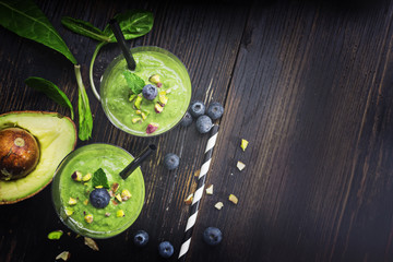 Smoothie with green spinach, pistachio and avokado on dark wooden board. Well being and weight loss concept.