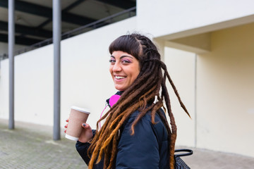 Urban Young Woman with Dreadlocks holding a Cup of Coffee Outdoors