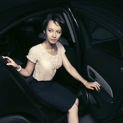 Young fashion woman in white blouse and black skirt sitting in car