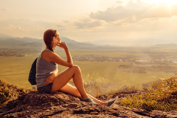 Cheerful woman is having rest on edge of cliff and looking at sun valley and mountains