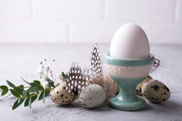 Easter  festive table setting with  quail eggs  and chicken egg standing in the egg cup with leaf sprigs of eucalyptus. On a gray concrete background.