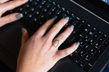 Female Hand with Heart Tattoo Using Laptop Keyboard