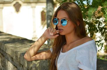 Chica joven con gafas de sol de espejo sentada en el banco de un pueblo