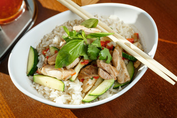 Asian riсe with pork and vegetables in oval plate with bamboo sticks