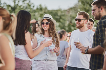 Group of people standing and drinking at the summer outdoor party