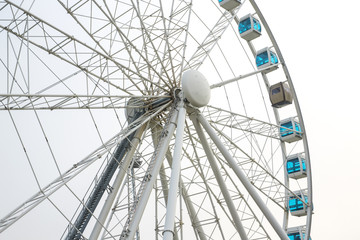 Detail of a large and high Ferris wheel with poles and white irons. The cabins have blue glass and there is none.