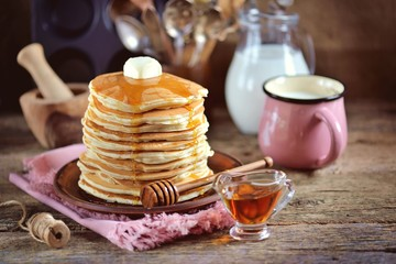 Homemade lush pancakes with milk and syrup on an old wooden background.