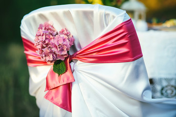 White chair decorated with pink hydrangeas outdoor for wedding or other event.
