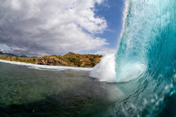 perfect barrel wave breaking over a shallow coral reef on a tropical island in indonesia with blue dramatic skies