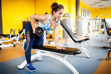 Girl goes in for sports in the gym. Concept of a healthy lifestyle.