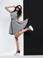 fashion portrait of a woman. young beautiful girl in grey dress and sunglasses posing in Studio on black and white background