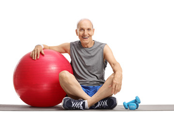 Elderly man with a pilates ball and dumbbells sitting on an exercise mat