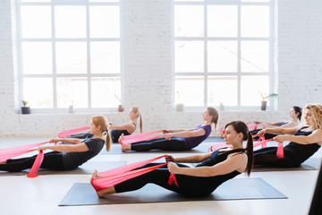Group of six women are doing stretching exercise with red resistance bands in white studio interior. Teamwork, good mood and healthy lifestyle concept.