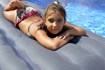 Portrait of a girl in bikini sunbathing on an inflatable mattress in swimming  pool