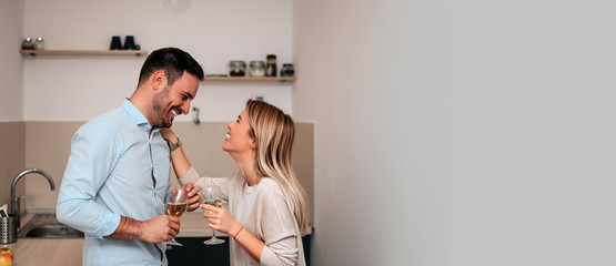 Attractive couple in kitchen talking and smiling.