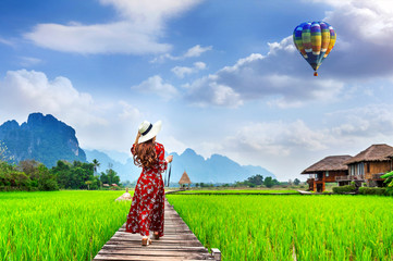 Young woman look at balloon and walking on wooden path with green rice field in Vang Vieng, Laos.