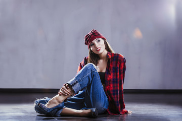 Young beautiful model posing in jeans, shirt and red checkered hat against a gray wall in the Studio