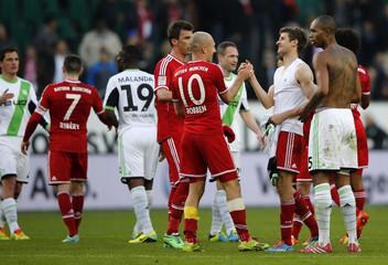 Bayern Munich and Wolfsburg players react after their German first division Bundesliga soccer match in Wolfsburg