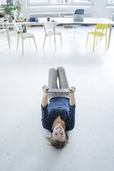 Portrait of laughing young woman with tablet lying on the floor in a loft