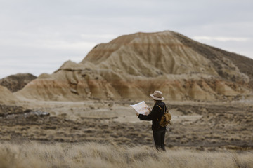 Woman with map standing in barren landscape