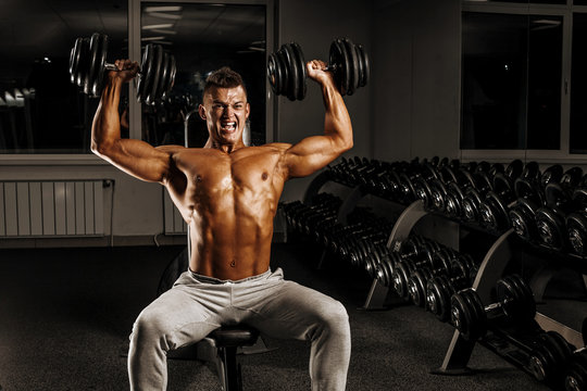 Brutal strong athletic men pumping up muscles and train in gym workout bodybuilding concept background