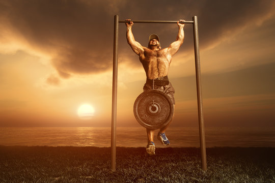 Strong man pulled on the bar at sunrise on the shores of lake