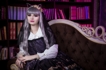 A beautiful woman in the form of lolita, dolls with cat ears sitting on the sofa in the library. Japanese street fashion.