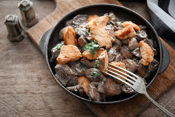 Frying pan with delicious mushrooms and meat on table