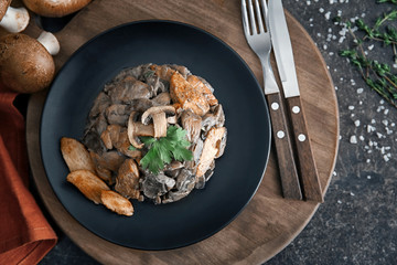 Plate with delicious mushrooms and meat on wooden board